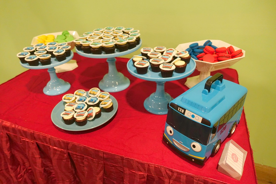 A cute dessert table setup with Tayo bus themed macarons and cupcakes!